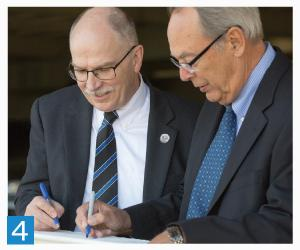 4. Dean Latta and dean emeritus Wayne Barkmeier, DDS, MS, at the beam-signing for the new School of Dentistry building.