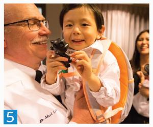 5. Dean Latta holds Itsuki Andrew Takamizawa, who was visiting Omaha from Tokyo with his family. Itsuki — who was given Latta's middle name as a tribute to the dean — was born in Omaha while his father was a visiting professor and researcher at Creighton.