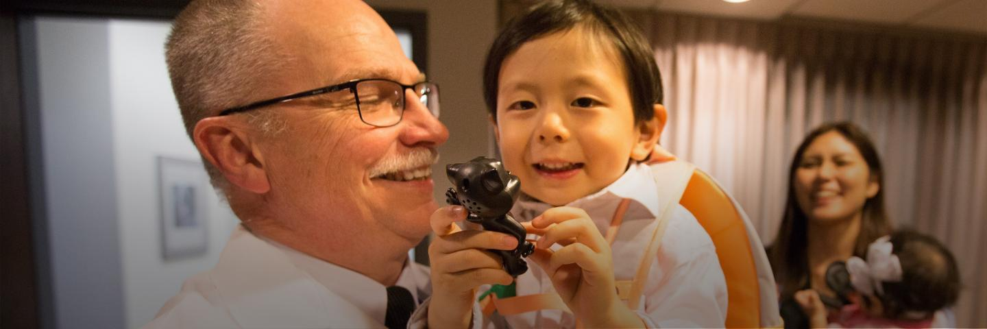 Dean Latta holds Itsuki Andrew Takamizawa, who was visiting Omaha from Tokyo with his family. Itsuki — who was given Latta's middle name as a tribute to the dean — was born in Omaha while his father was a visiting professor and researcher at Creighton.